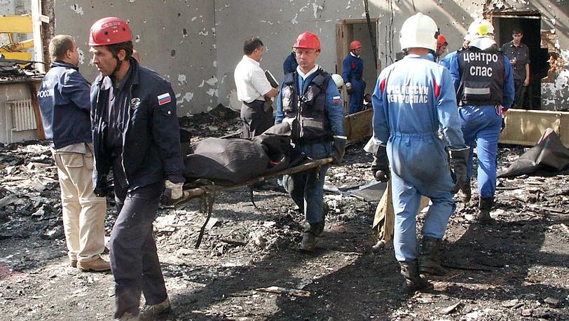 Спасатели МЧС РФ выносят тела погибших заложников из разрушенного здания школы. Фото ИТАР-ТАСС/ Андрей Югов