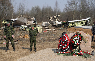 Russian soldiers standing in line around wreckage of a Polish government Tupolev Tu-154 plane that crashed near Smolensk airport