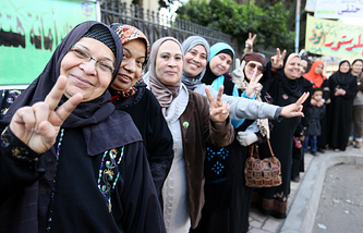 An Egyptian Women flashes a V for Victory sign' as she waits in line to vote outside polling station during the first day of voting on the new constitution