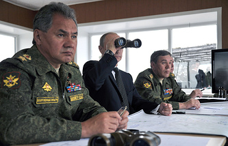 Vladimir Putin (C) and Sergei Shoigu (L) watch military drills in July 2013