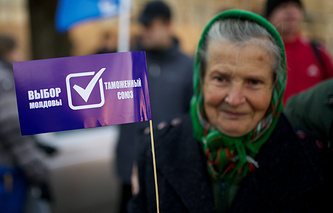 """A woman in Moldova with a flag running: """"Customs Union"""", """"Moldova's choice"""" (archive)"""