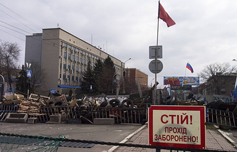 """Barricades and Soviet era red and Russian national flags with a poster reading """" Stop, no entrance! """" in front of the Ukrainian regional office of the Security Service in Luhansk"""