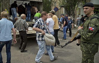 People carry sand bags to set up a shooting position in Donetsk