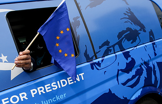 A supporter waves the European Union flag from the campaign van of Luxembourgian Jean-Claude Juncker