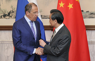 Russian Foreign Minister Sergei Lavrov (L) shakes hands with Chinese Foreign Minister Wang Yi