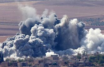 Smoke rises after an apparent US-led coalition airstrike on Minaze village near Kobane, Syria
