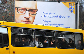 A bus drives past a poster featuring Ukraine's Prime Minister Arseniy Yatsenyuk