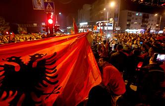 Kosovo Albanians react with Albanian flags in center of Kosovo's capital Pristina, 15 October 2014