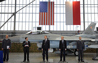Polish and US officials stand in front of a F-16 fighter jet during the contract signing ceremony of 40 Lockheed Martin's joint air-to-surface standoff missiles (JASSM)