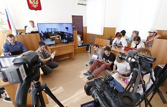 Journalists watching former Ukrainian pilot Nadezhda Savchenko (on the screen) trial