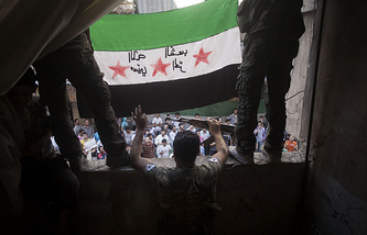 Free Syrian Army rebels holding a revolutionary flag