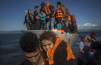 Migrants and refugees disembarking from a vessel after their arrival from the Turkish coast to the northeastern Greek island of Lesbos