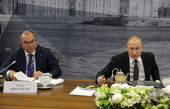 TASS Russian News Agency Director General Sergei Mikhailov (L) and Russia's President Vladimir Putin