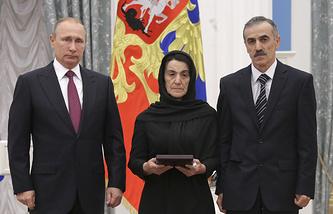 Russia's President Vladimir Putin and parents of Dagestani police officer Magomed Nurbagandov