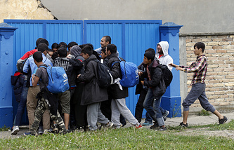 Migrants stop and take some food as they walk toward the Serbian border with Hungary in the village of Nova Pazova, Serbia