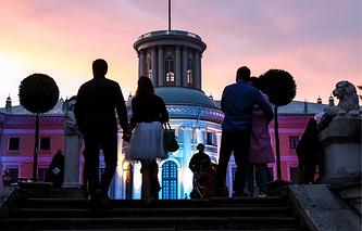 Visitors walk outside a lit mansion at Usadba Jazz International Festival in Arkhangelskoye Estate