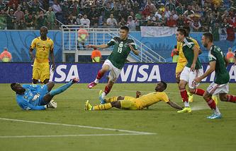 Обире Перальта (в центре, №19) отправляет мяч в ворота сборной Камеруна