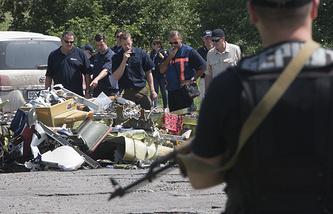 Иностранные специалисты и члены миссии ОБСЕ у фрагментов самолета. Донецкая область