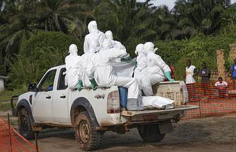 Либерия. Медики в защитных костюмах с телом человека, погибшего от лихорадки Эбола