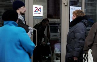 В связи с повышенным спросом на снятие вкладов банкоматы в Екатеринбурге пополняются несколько раз в день. На фото: клиенты банка ждут в очереди, пока инкассатор пополняет банкомат