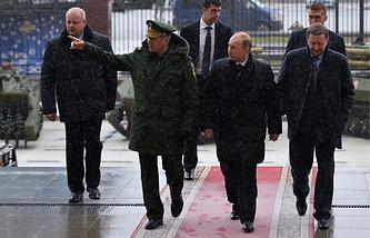 Министр обороны РФ Сергей Шойгу, президент России Владимир Путин и руководитель администрации президента РФ Сергей Иванов (слева направо на первом плане) у здания Минобороны РФ