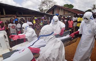 Медицинские работники несут тело человека, погибшего от вируса Эбола, Либерия, декабрь 2014 года