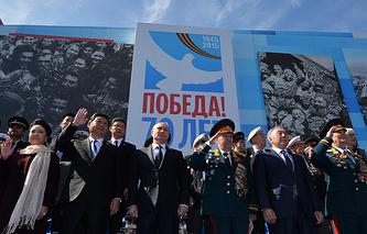 Президент России Владимир Путин (в центре), председатель Китайской Народной Республики Си Цзиньпин с супругой Пэн Лиюань (слева) и президент Казахстана Нурсултан Назарбаев (второй справа) во время военного парада на Красной площади