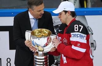 Президент Международной хоккейной Федерации Рене Фазель и игрок сборной Канады Сидни Кросби с кубком за победу в финальном матче чемпионата мира по хоккею между сборными Канады и России