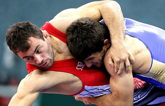 Джумбер Квелашвили и Аниуар Гедуев (в синем) в полуфинальных соревнованиях по вольной борьбе в весовой категории до 74 кг