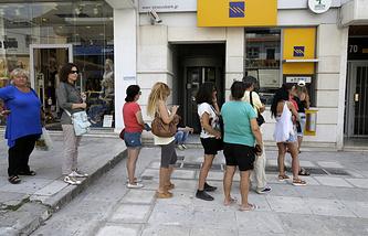 Жители Афин стоят в очереди, чтобы снять наличные в банкомате