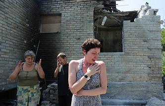 Местные жители у жилого дома, частично разрушенного в результате ночного обстрела в Горловке