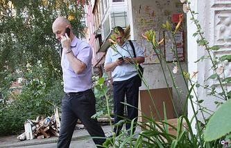 Сотрудники правоохранительных органов у подъезда жилого дома, где произошло убийство