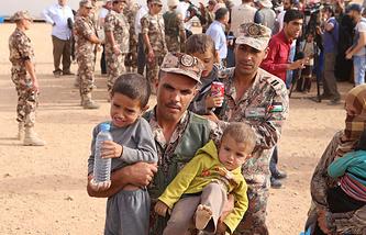 Иорданский солдат несет детей сирийских беженцев