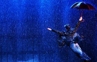 """Актер Станислав Чунихин в сцене из мюзикла """"Поющие под дождем"""""""
