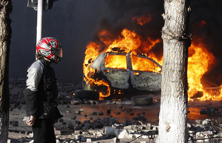 A protester seen near a burning vehicle in central Kiev