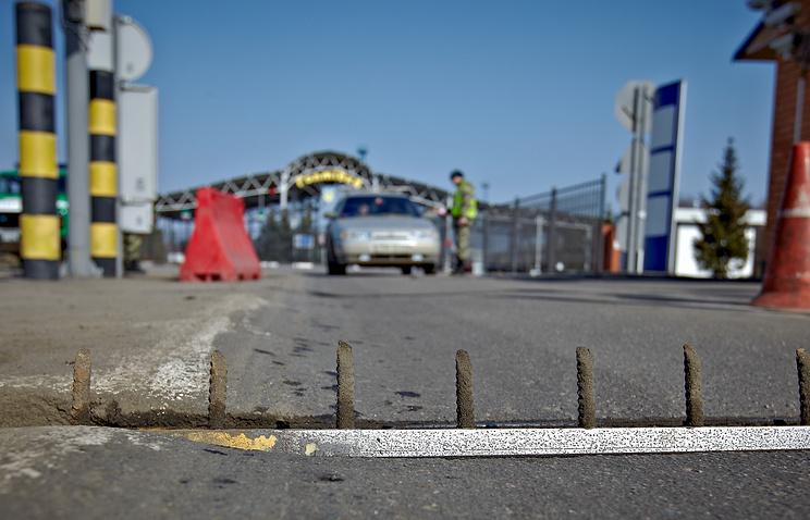 Ukrainian border guard stops a car which crosses a Russia - Ukraine border near of Goptivka village, about 35 km of Kharkiv