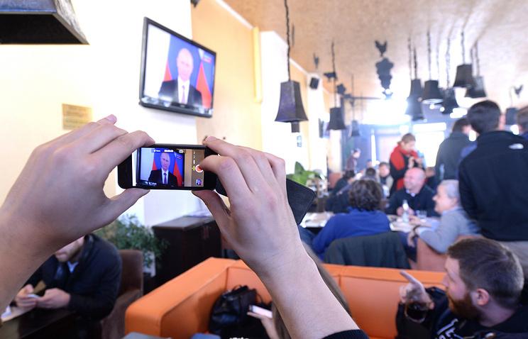 People watching Vladimir Putin's address in Crimea's Simferopol