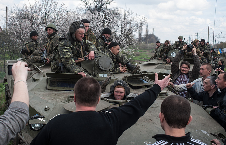 People block a column of Ukrainian Army combat vehicles on their way to the town of Kramatorsk