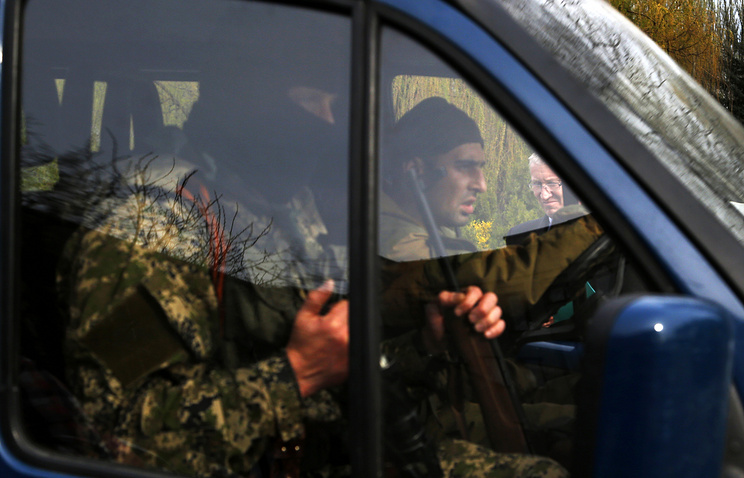 OSCE special mission in Ukraine official Mark Etherington seen in the background when a car with armed men drives past