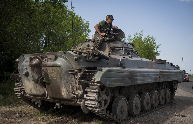Ukrainian soldier standing guard from a tank at a checkpoint in Mariupol