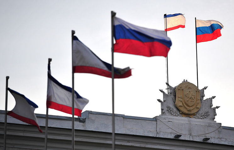 Crimean and Russian flags on the roof of the State Council building