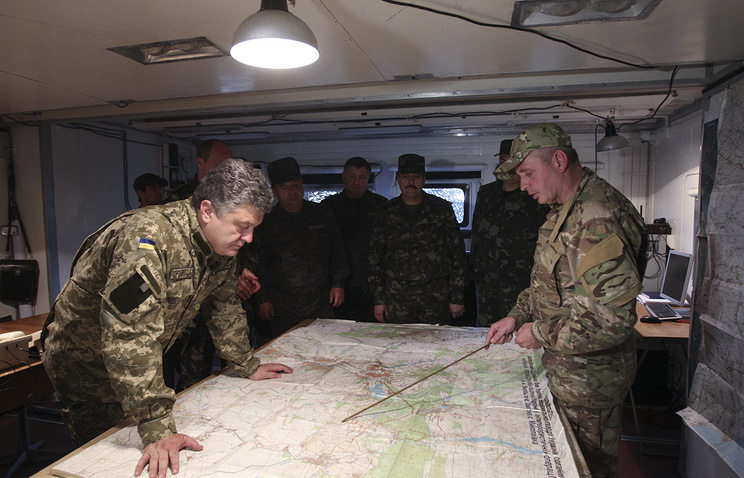 Ukrainian President Petro Poroshenko (left) listens to a report at a staff of the military operation in south east Ukraine