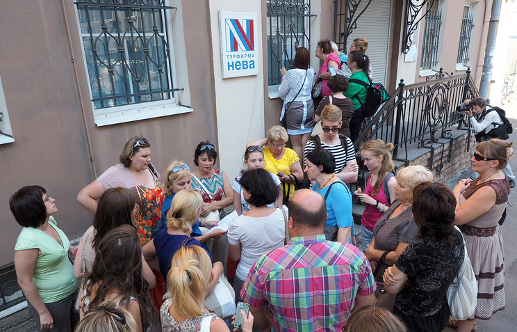 People gather in front of the travel agency's office