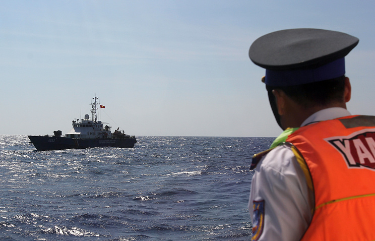 A Vietnamese coast guard officer looking at a Vietnamese coast guard vessel in the South China Sea