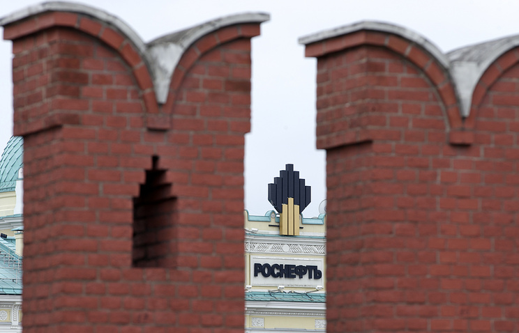 Headquarters of the Rosneft oil company with its logo seen through the walls of Moscow Kremlin