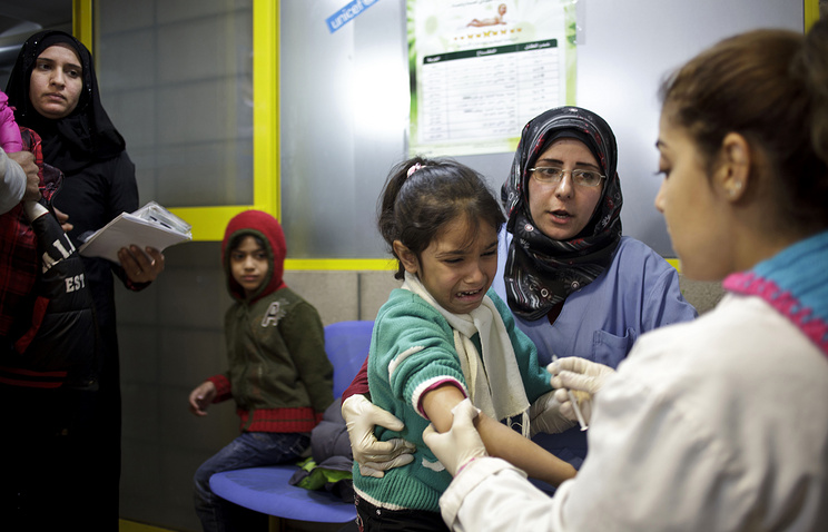 Syrian girl weeps after receiving the measles vaccine from a UNICEF nurse