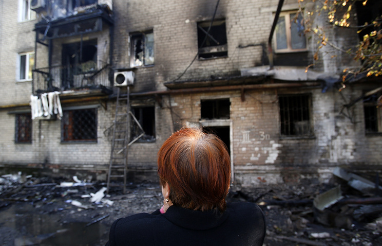 A woman looks at her house destroyed in a shelling attack on Donetsk
