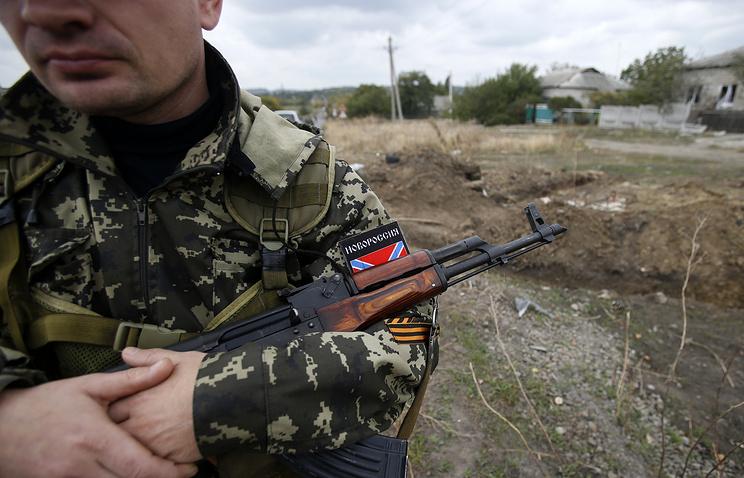A militia fighter guards a mass grave