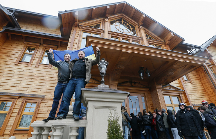 Ukrainians wave a national flag as they pose in front on of the main buildings in the residence of Ukrainian President Viktor Yanukovych