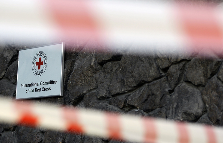 A damaged sign on a Red Cross office seen behind police tape after shelling in Donetsk